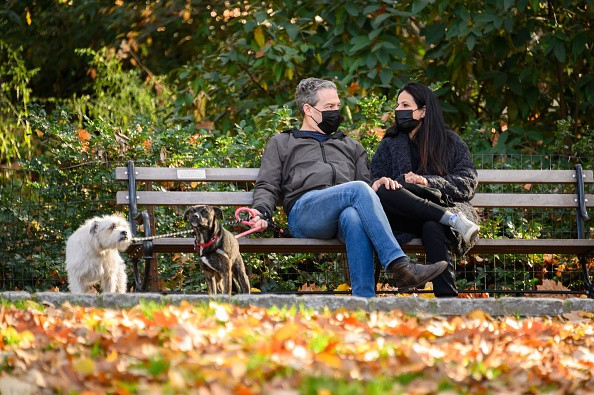 People sit with their dogs in Riverside Park as the city continues...