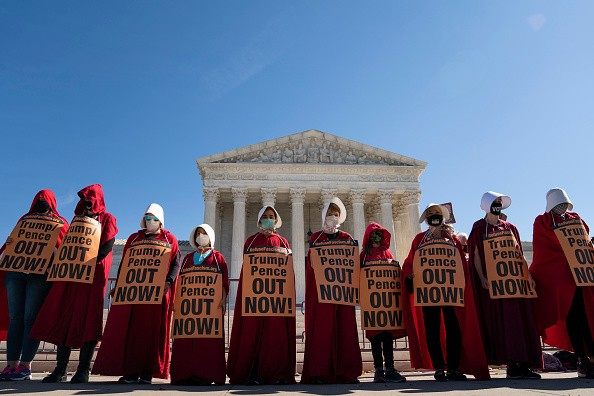 Dressed as handmaids, opponents of Supreme Court nominee Judge Amy...