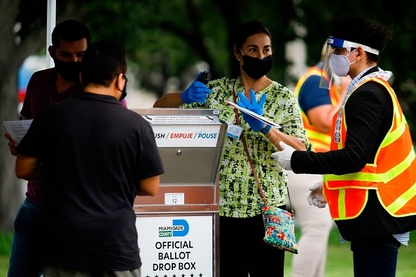 Poll workers are seen at a ballot drop box at Miami-Dade County...