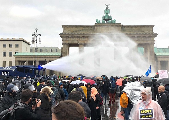Police use water cannons at the Brandenburg Gate during a...