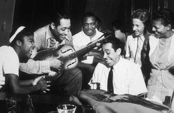 American composer and bandleader Duke Ellington plays guitar and Cab...