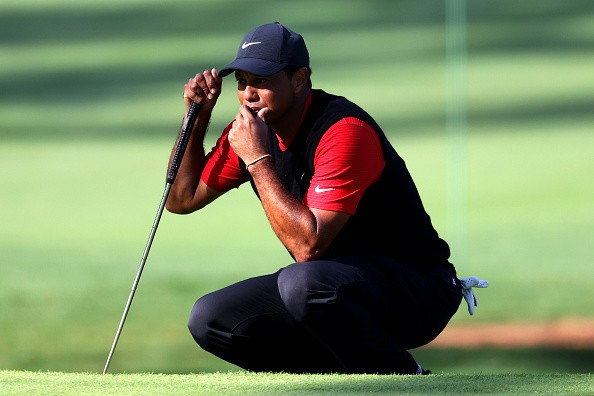 Tiger Woods of the United States lines up a putt on the seventh green...
