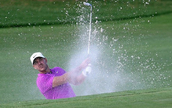 Brooks Koepka of the United States plays a shot from a bunker on the...