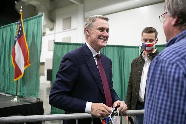 U.S. Sen. David Purdue talks with a supporter