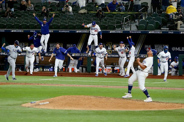The Los Angeles Dodgers celebrate after Julio Urias strikes out Willy...