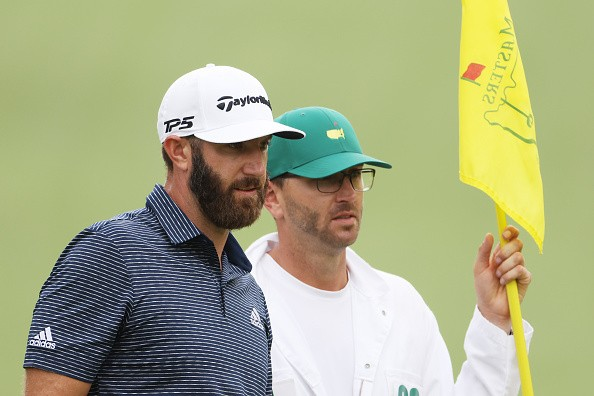 Dustin Johnson of the United States stands with caddie Austin Johnson...