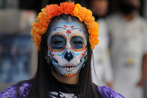 A person with their face make-up as skull to celebrate the Mexican...