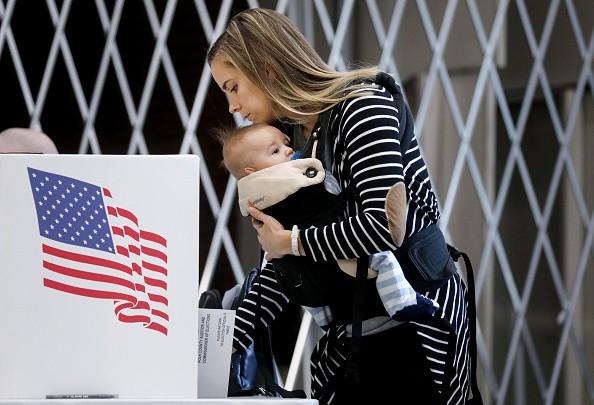 Voter Izzi Buckles holds her son Rowan as she marks her ballot