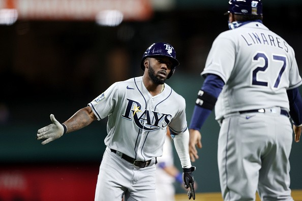 Randy Arozarena of the Tampa Bay Rays is greeted by Third Base Coach...