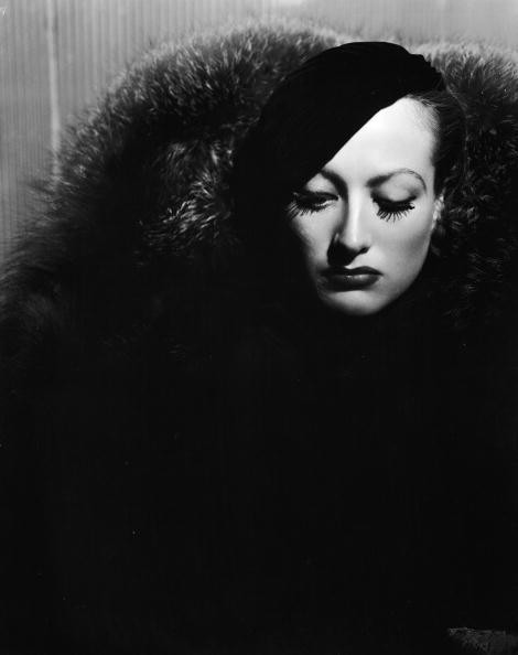 American actress Joan Crawford wearing a beret and a large fur coat.