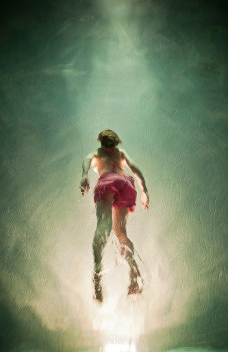 Girl swimming underwater in pool at night, lit with underwater light.