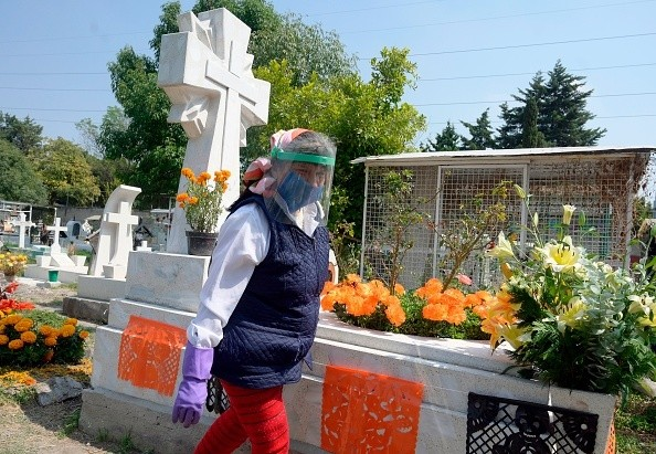 A woman visits a relative's grave prior to the Day of the Dead at the...