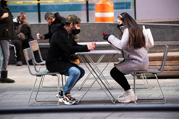 People wear face masks at an outdoor dining area in Times Square as...