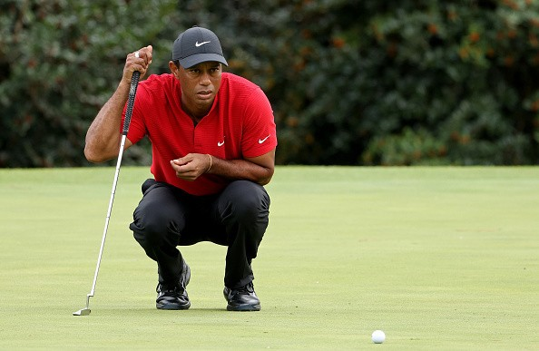 Tiger Woods of the United States lines up a putt on the 14th green...