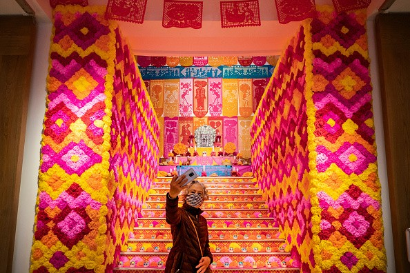 A woman takes a selfie in front of the offerings altar during the Day...