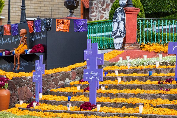 Crosses, cempasuchil flowers, candles and skeletons are placed in the...