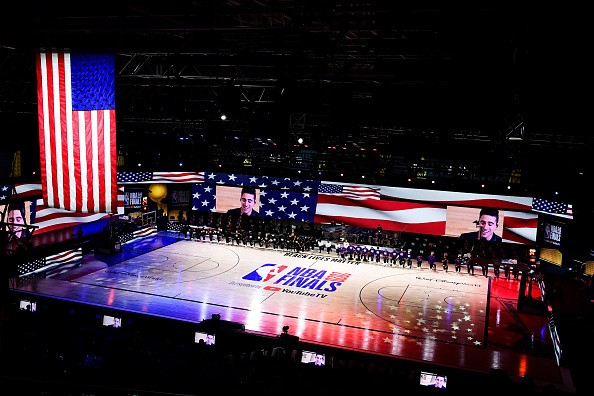 The Los Angeles Lakers and the Miami Heat kneel during the National...