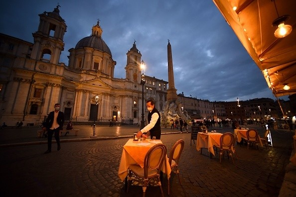 An employee cleans up a table on an empty terrace at Piazza Navona