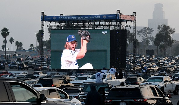 Clayton Kershaw of the Los Angeles Dodgers pitches as fans look on a...