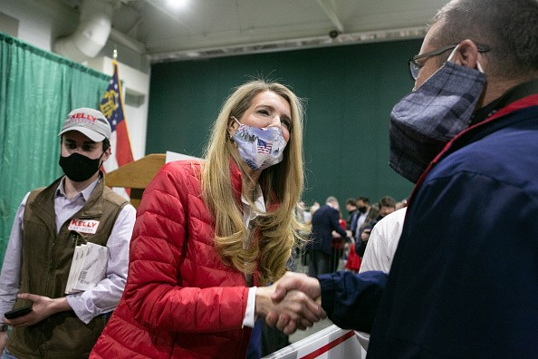 U.S. Sen. Kelly Loeffler shakes hands with a supporter during a rally