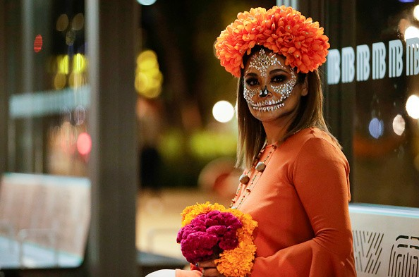 A woman wears a orange dress and painted as skull, poses for photos...