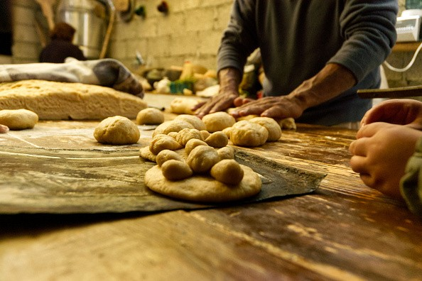 A baker during the preparation of the traditional bread of the dead ....