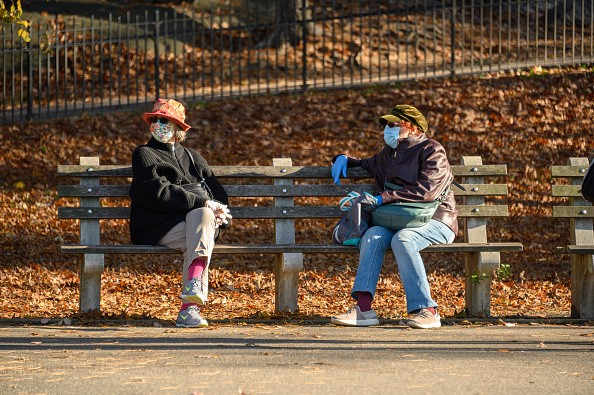 People wear face masks and rubber gloves in Riverside Park as the...