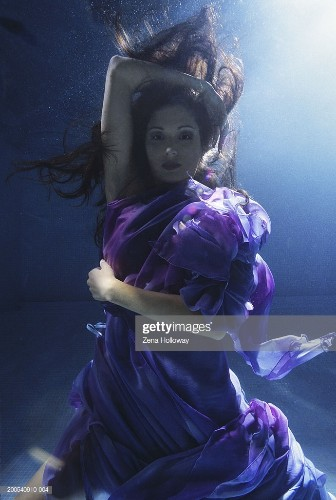Young woman wrapped in silk, underwater view, portrait