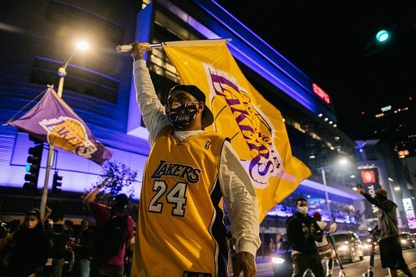 A Lakers fan walks with a Lakers flag in front of the Staples Center...