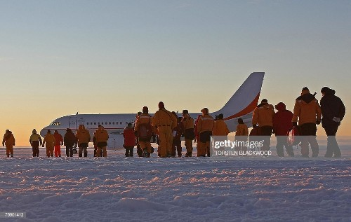 Passengers, scientists, government officials and ground crew walk on...