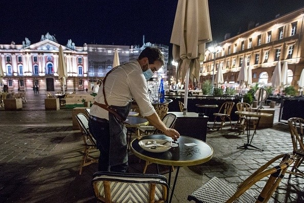 An employee tides up the tables on the terrace of a closing bar on...