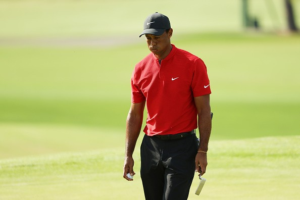 Tiger Woods of the United States reacts after putting on the 18th...