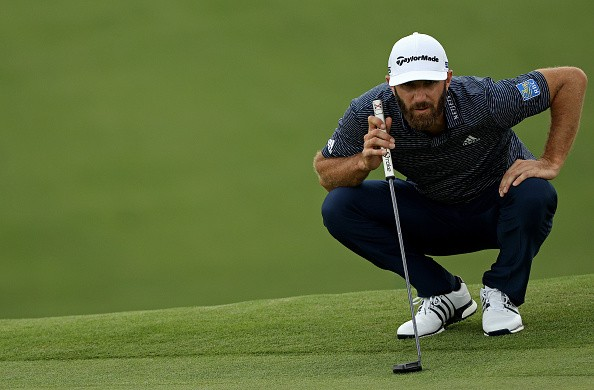 Dustin Johnson of the United States lines up a putt on the ninth...
