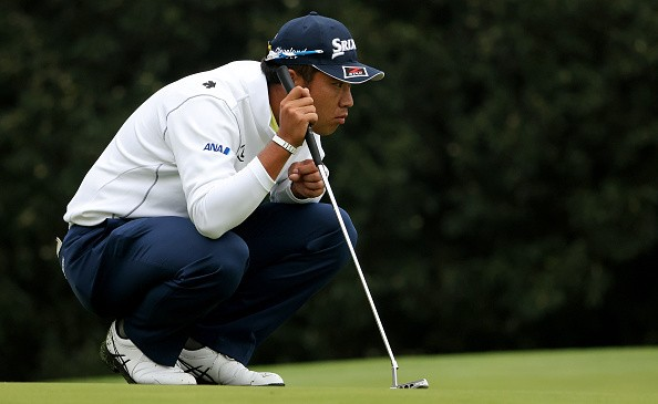 Hideki Matsuyama of Japan lines up a putt on the first green during...