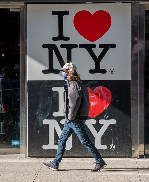 A person wears a face mask by an 'I love NY' sign in Times Square as...