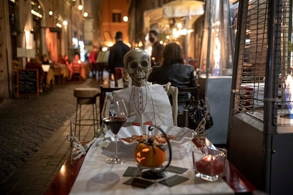 A skeleton is seen at a restaurant table to protest against the new...