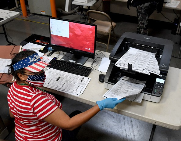 A Clark County election worker scans mail-in ballots at the Clark...