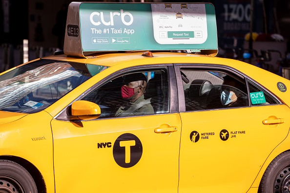 A driver and a passenger wear face masks in a yellow cab as the city...