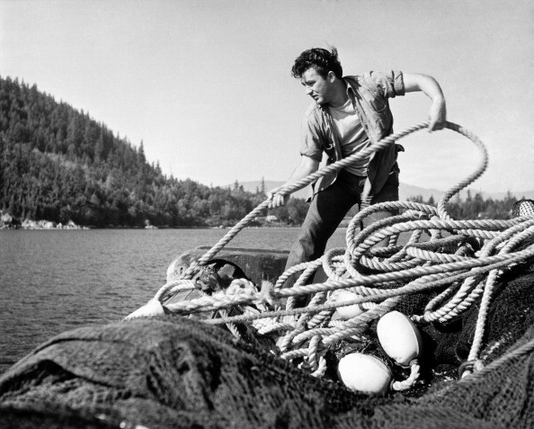 View of a fisherman pulling on a rope and hauling in a large net,...