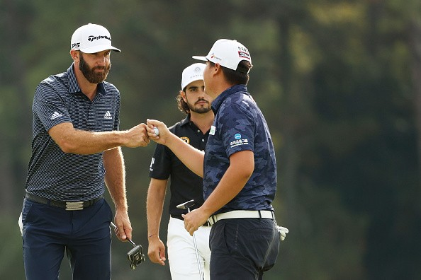 Dustin Johnson of the United States reacts with Sungjae Im of Korea...