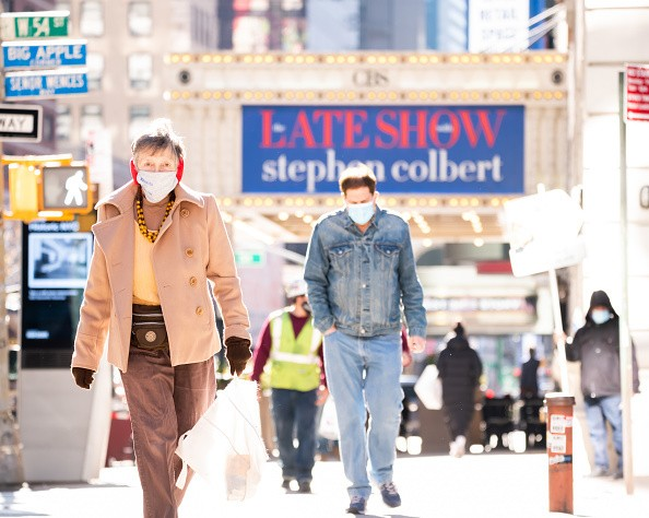 People walk outside The Late Show with Stephen Colbert at the Ed...