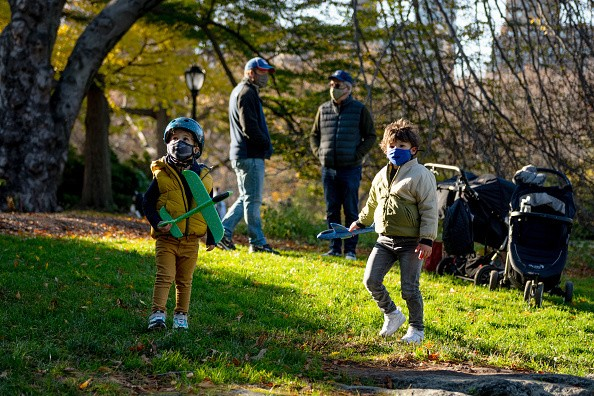 Kids wearing masks play with model airplanes in Central Park on...