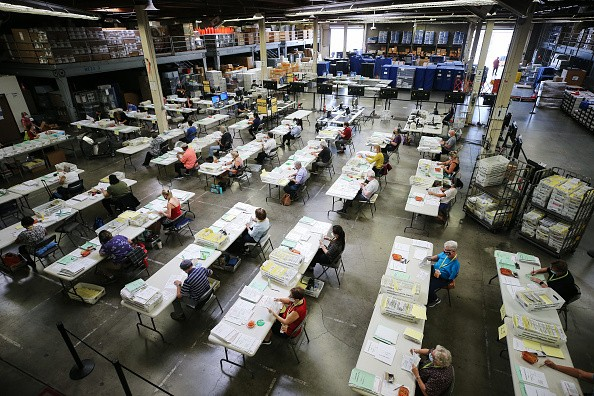 Election workers process mail-in ballots at the Orange County...