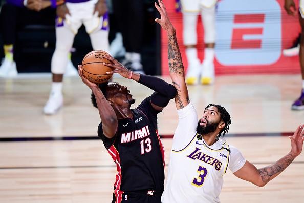 Bam Adebayo of the Miami Heat drives the ball against Anthony Davis...