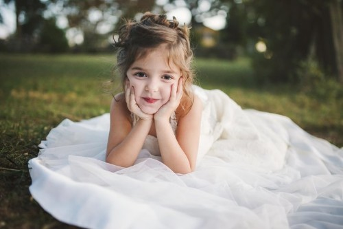 Little Girl Poses In Late Mother's Wedding Dress In Beautiful Photo Shoot