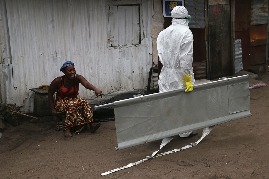 Ebola in Liberia: Powerful Photos of Families' Agony as Loved Ones are Removed for Cremation