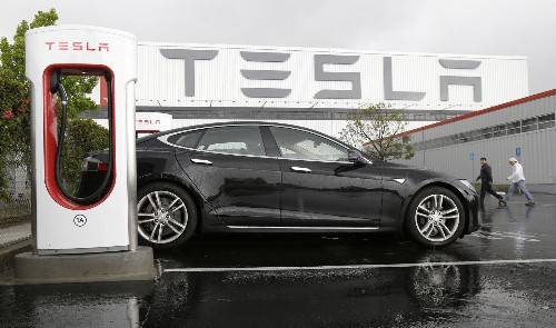 Tesla cuts annual production forecast; second-quarter loss widens
