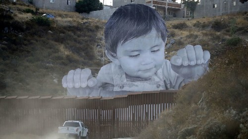 Giant portrait of toddler peers over U.S.-Mexico border wall