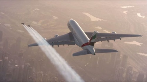 Two guys wearing jetpacks fly alongside an Airbus A380