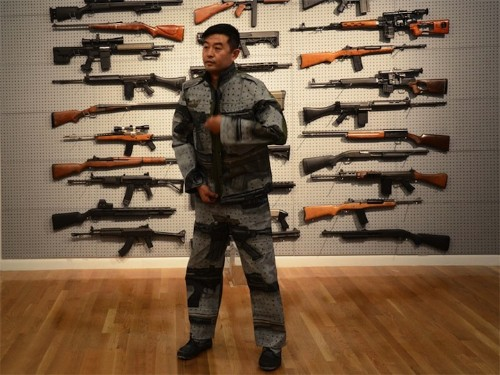 Liu Bolin Camouflages Himself into a Rack of Guns